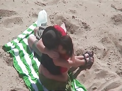 Kissing and tit sucking on the beach with a couple tubes
