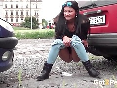 Girl squats between parked cars to pee tubes