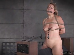 Clamps and weights hang off her sensitive nipples tubes