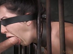 Chained slave in a cage opens her mouth for face fucking tubes