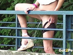 Shaved pussy girl takes a piss off the bridge tubes