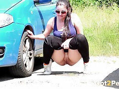 Big ass girl goes pee in a parking lot tubes