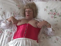 Old babe in a lovely corset fondles her tits tubes