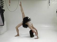 Ballerina in a black dress does standing splits tubes