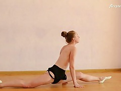 Blonde ballerina stretches and bends in the nude tubes