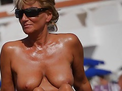Nice tanned milf with big boobs at the beach tubes